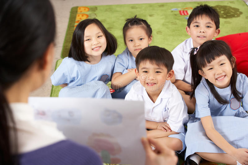 Teacher Showing Painting To Students. In Chinese School Classroom stock photography