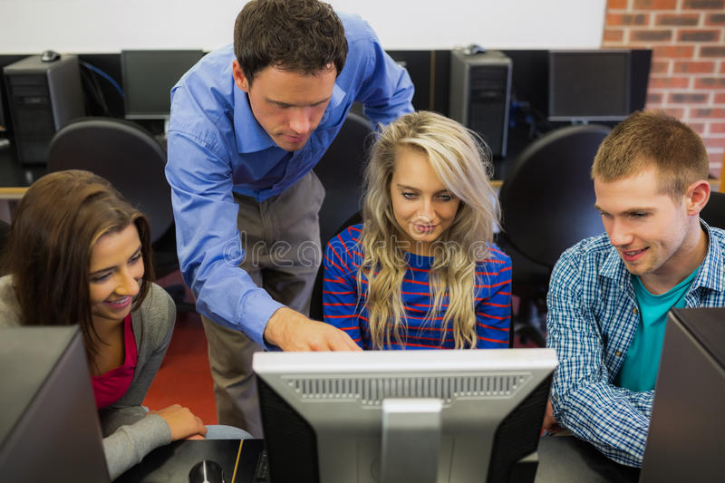 Teacher showing something on screen to students in computer room. High angle view of teacher showing something on screen to students in the computer room stock images