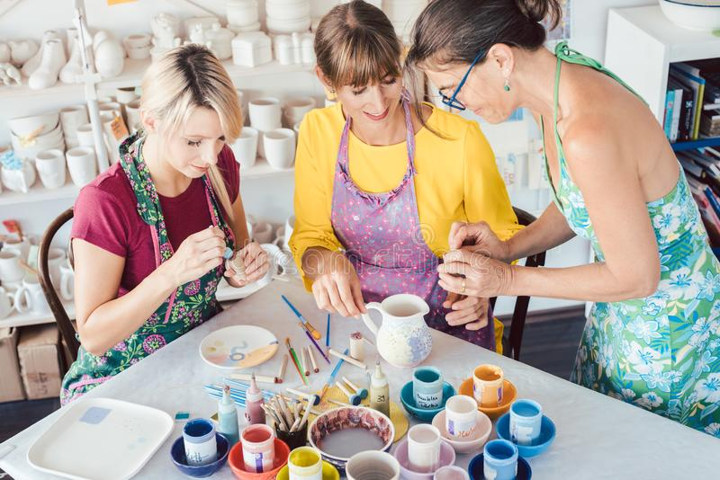 Teacher showing women in workshop how to paint self-made dishes stock image