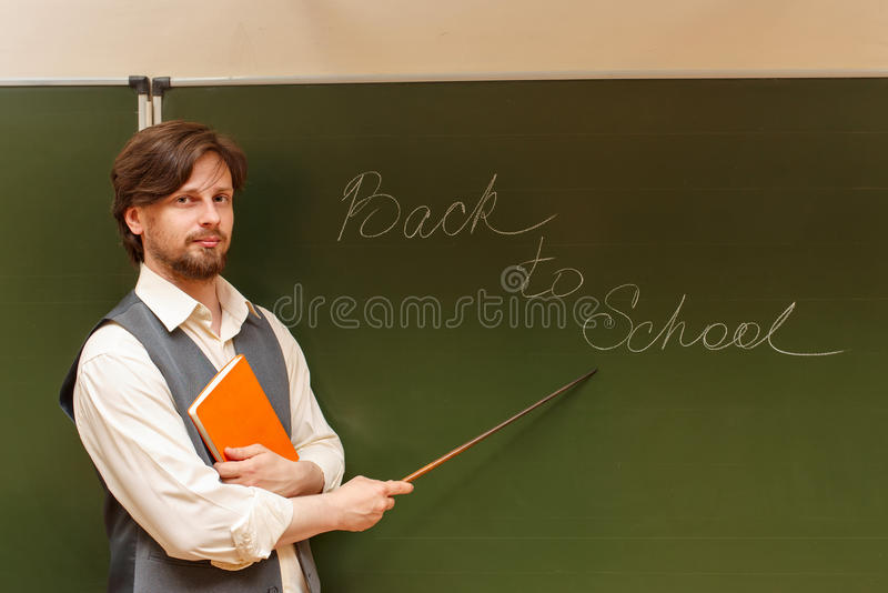 Teacher shows pointer on back to school. The teacher shows the inscription on the back to school. The inscription on the blackboard with chalk. The concept of stock image