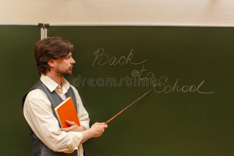Teacher shows pointer on back to school. The teacher shows the inscription on the back to school. The inscription on the blackboard with chalk. The teacher is stock photo