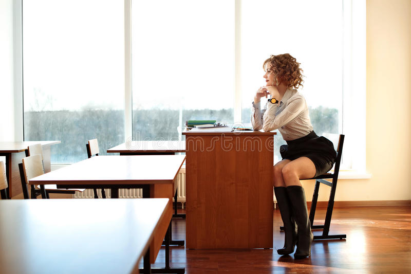 Teacher sit at the desk in the classroom and wait for students royalty free stock photography
