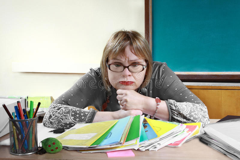 Teacher. Sits at desk in classroom with troubled expression on her face stock photography