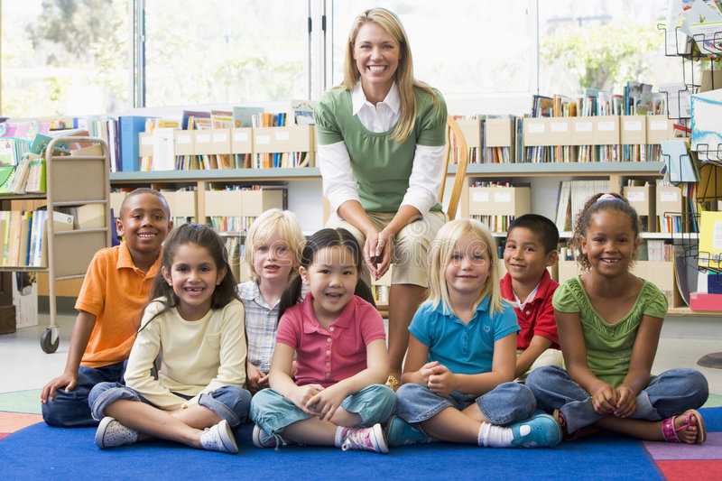 Download Teacher Sitting With Children In Library Stock Photo - Image: 6081786