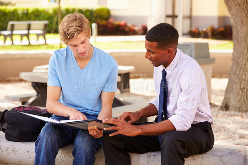 Teacher Sitting Outdoors Helping Male Student With Work stock photo