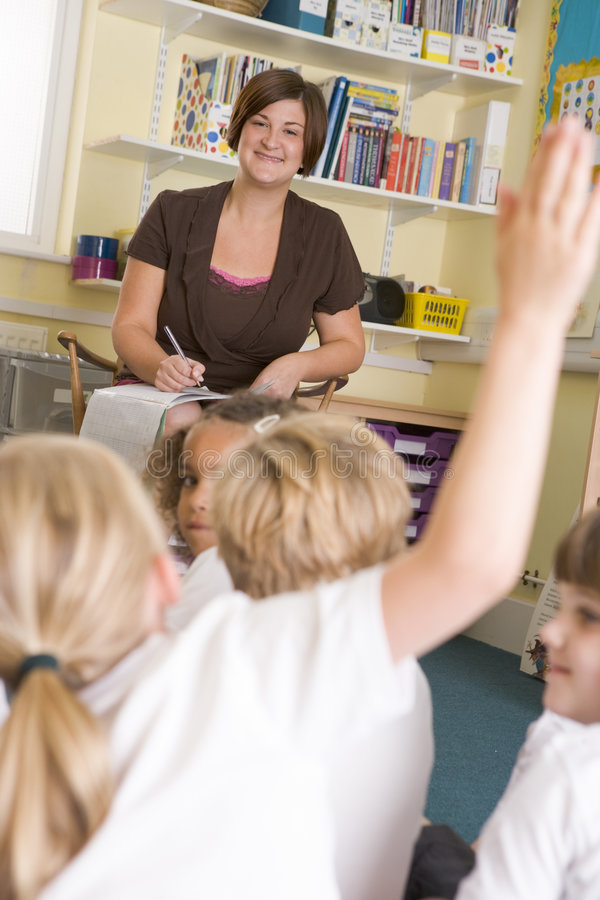 Download A Teacher Sitting With A Primary Class Stock Photo - Image of pupils, calling: 6080960