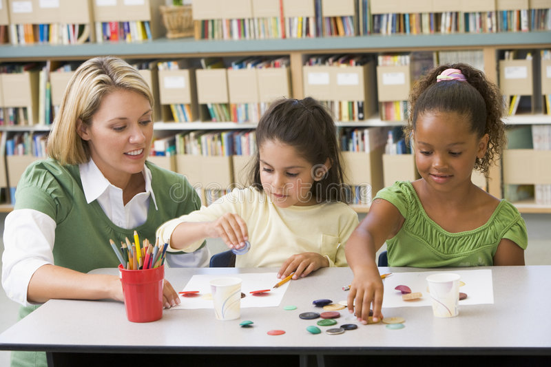 Teacher sitting with students in art class royalty free stock photography