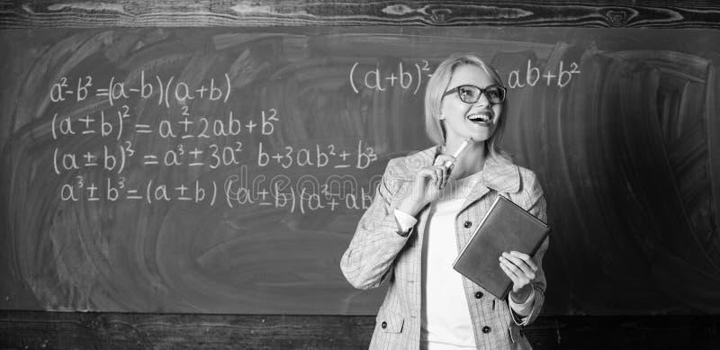 Teacher smart woman with book explain topic near chalkboard. What makes great teacher. School teacher explain things stock images