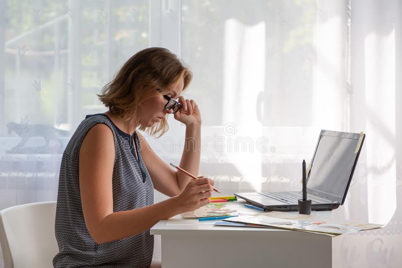 Teacher or speech therapist at work. Young woman with glasses sitting at the table and working with materials for children. Nearby royalty free stock images