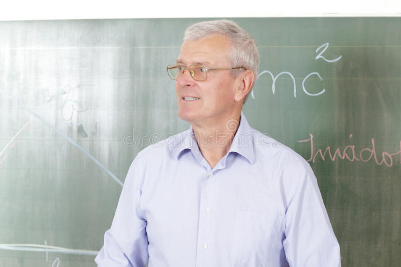 Teacher standing in classroom royalty free stock photography