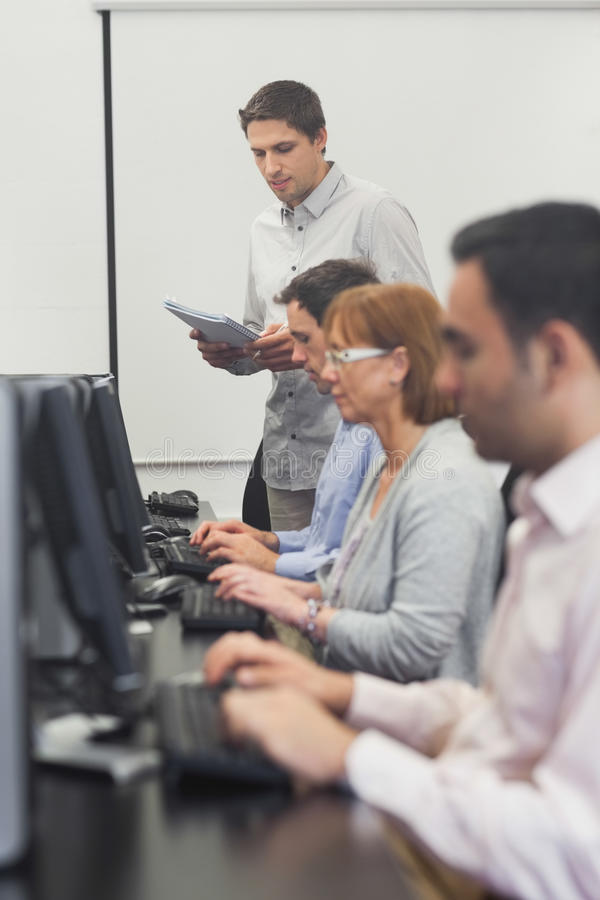 Download Teacher Standing In Front Of Computer Class Stock Photo - Image: 35781478
