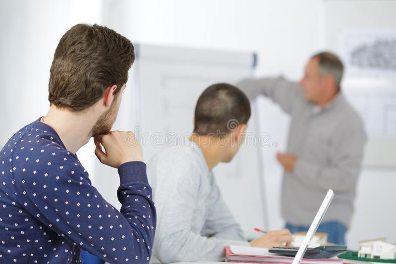 Teacher standing in front white board in classroom. Teacher standing in front of white board in classroom royalty free stock image