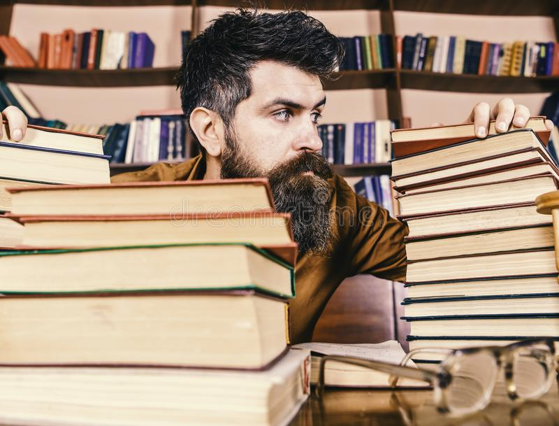 Teacher or student with beard sits at table with glasses, defocused. Bibliophile concept. Man on strict face between. Piles of books, while studying in library stock photography