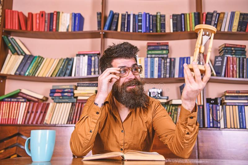 Teacher or student with beard studying in library. Scientist with eyeglasses sits at table and looks at hourglass. Man. On busy face reading book, bookshelves royalty free stock image