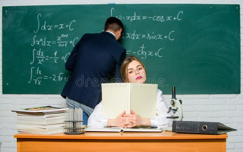 Teacher and student near chalkboard. College university education. STEM faculty. Man writing on chalkboard math formulas royalty free stock image