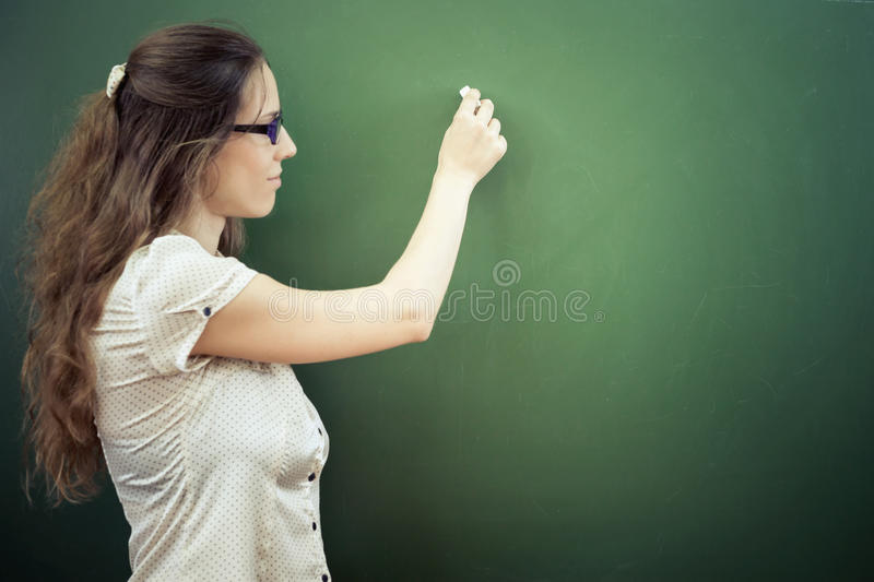 Teacher or student wrote on blackboard with chalk at classroom. At school or university. Concept of knowledge day and first of september stock images