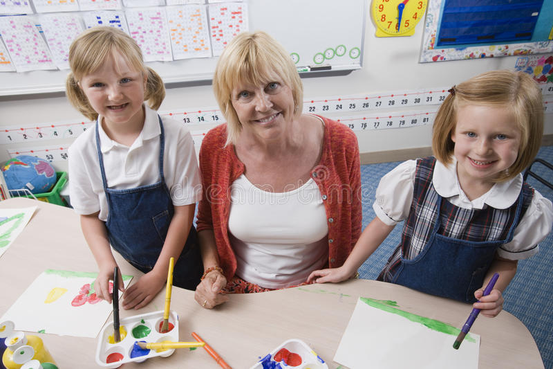 Teacher With Students In Art Class. Teacher assisting elementary students during art class stock photo