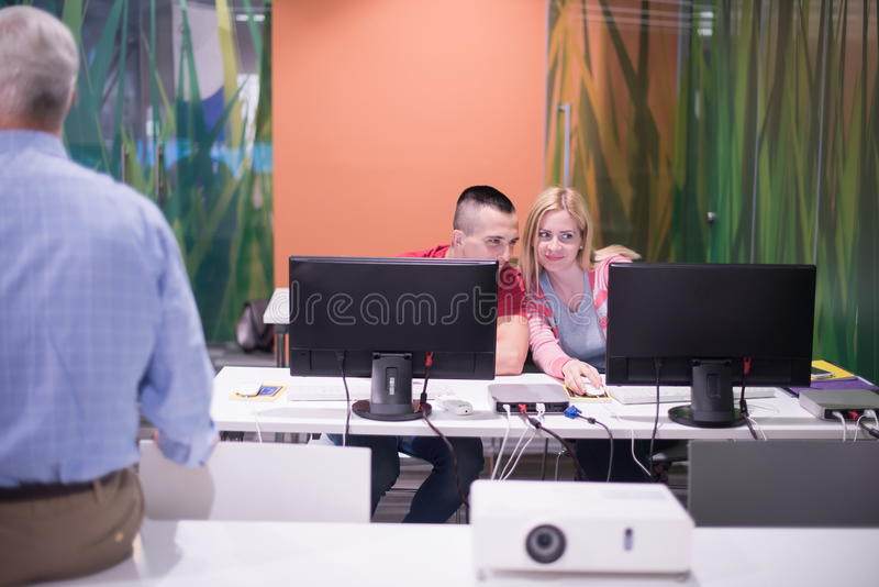 Teacher and students in computer lab classroom. Handsome mature teacher and students in computer lab classroom royalty free stock photography