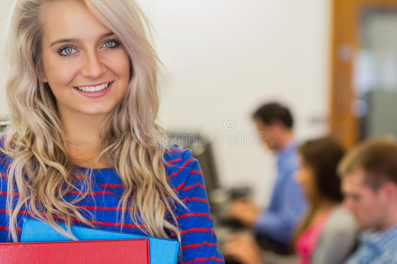 Teacher with students in the computer room. Portrait of a smiling teacher with young college students using computers in the computer room royalty free stock photo