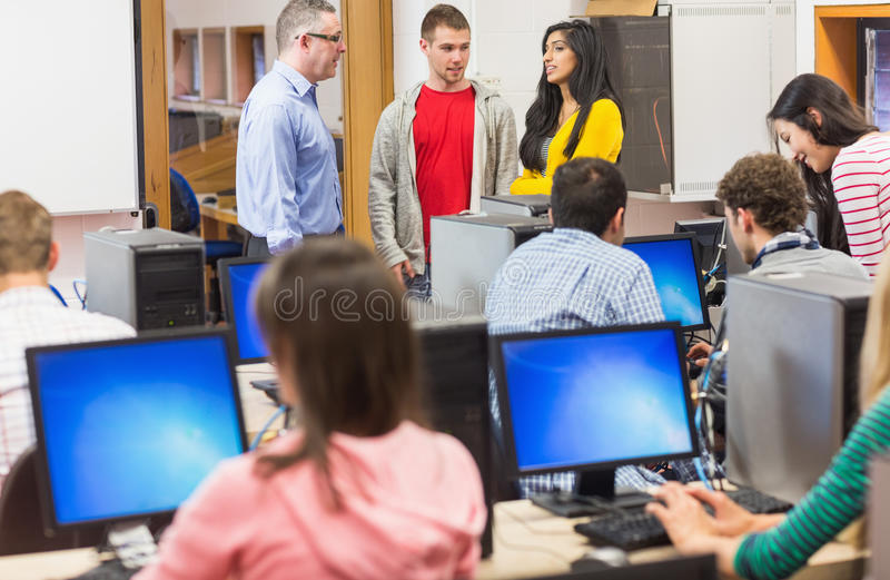 Teacher and students in the computer room. Teacher with young college students in the computer room royalty free stock photos
