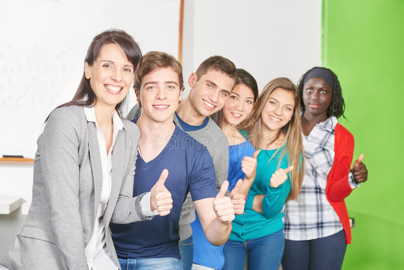 Teacher and students hold their thumbs up. In a high school classroom royalty free stock images