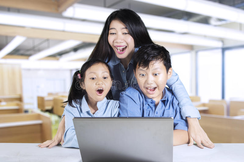 Teacher and students looking at laptop stock photo