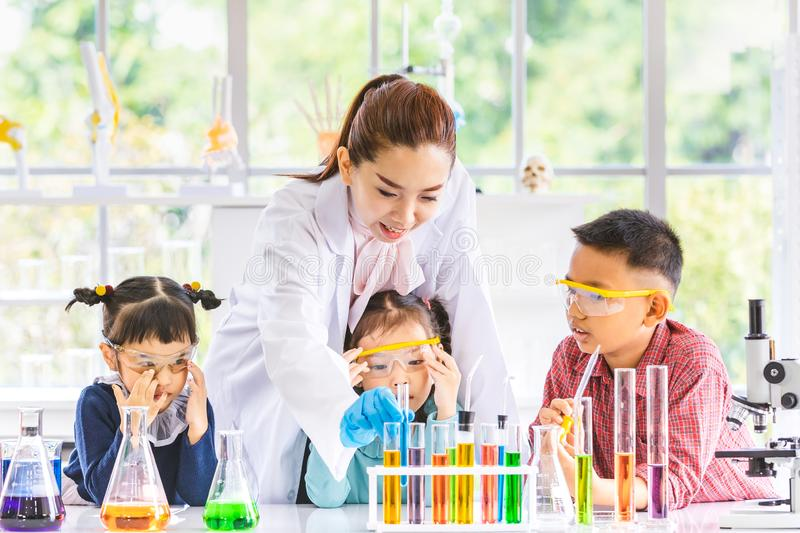 Teacher and students, smoke float out from blow. Science teacher teach Asian students about chemicals, smoke float out from blow, colorful test tube and royalty free stock image
