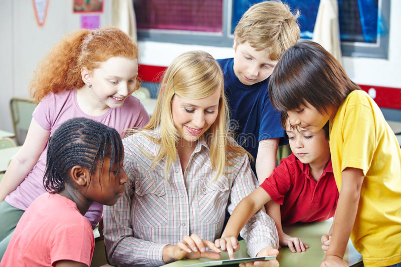 Teacher and students with tablet computer stock image