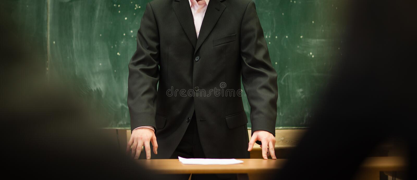 Teacher in front of a blackboard in a classroom royalty free stock images
