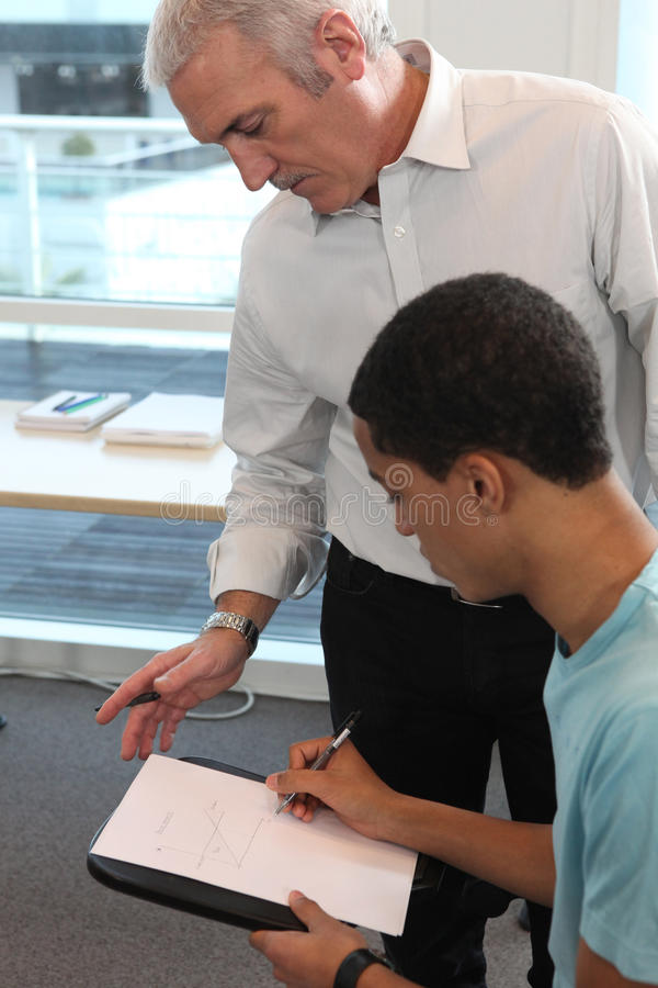 Teacher supervising his student's work. Teacher closely supervising his student's work stock photography