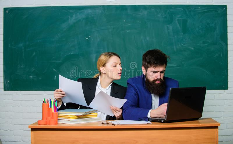 Teacher and supervisor working together in school classroom. School educator with laptop and principal with documents. Educational program. School education royalty free stock image