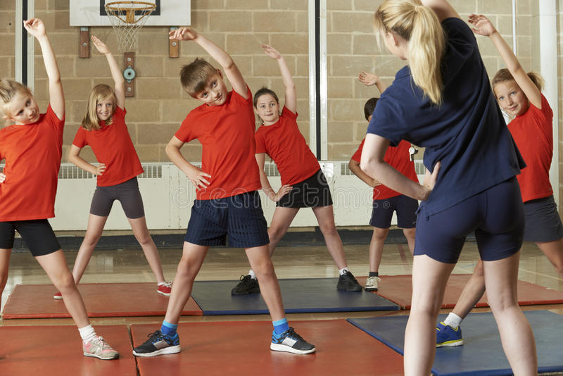 Teacher Taking Exercise Class In School Gym royalty free stock images