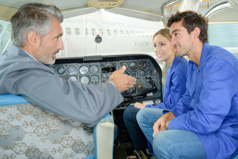 Teacher talking to students in aircraft cockpit royalty free stock photos