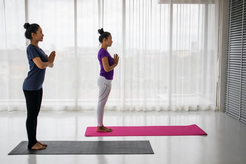 Teacher teach student to do yoga concept. A middle-aged Asian women is teaching another women to do yoga in a stretching position, where the teacher comes to royalty free stock images