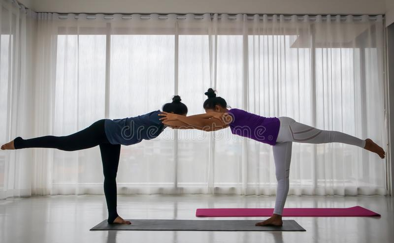 Teacher teach student to do yoga concept. A middle-aged Asian women is teaching another women to do yoga in a stretching position, where the teacher comes to royalty free stock photo
