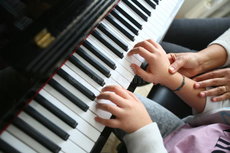 A teacher teaches playing piano her student. stock photo