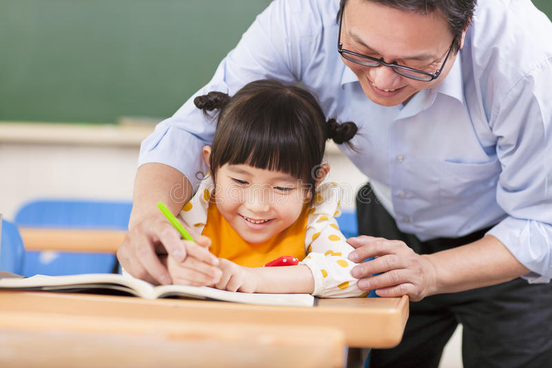 Teacher teaches a student to using a pencil stock image