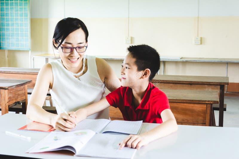 Teacher teaching boy to do homework stock images