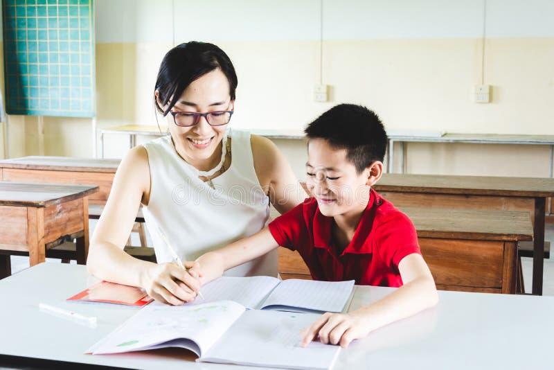 Teacher teaching boy to do homework stock image