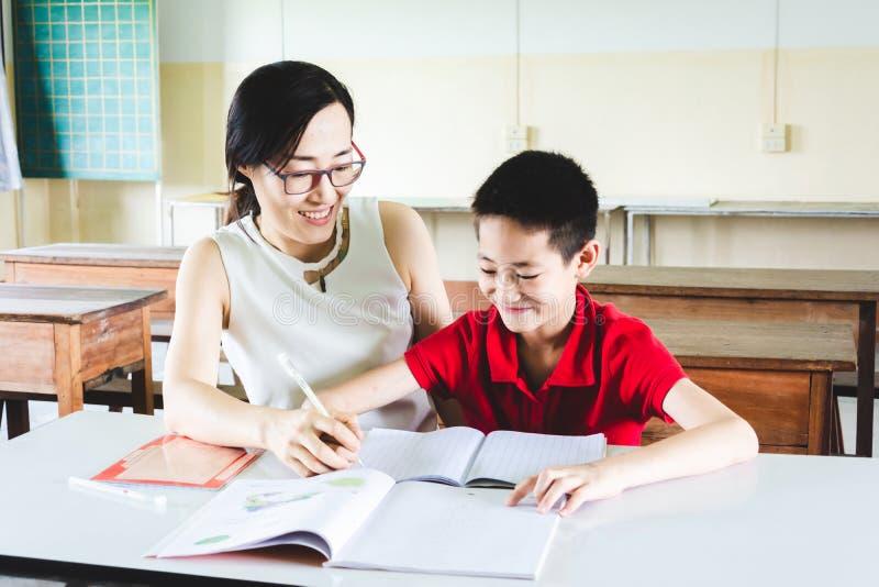 Teacher teaching boy to do homework royalty free stock photos