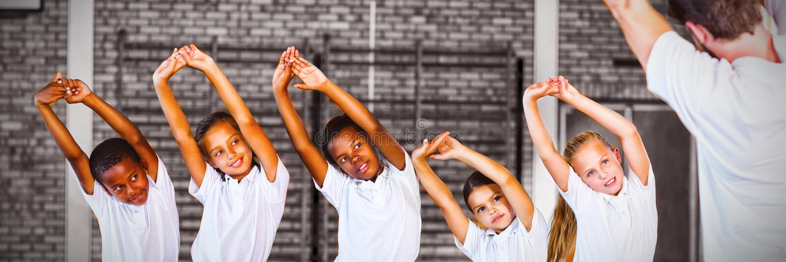 Teacher teaching exercise to school kids in basketball court. At school gym royalty free stock photos