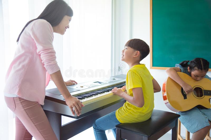 Teacher teaching kids playing Music Instruments stock images