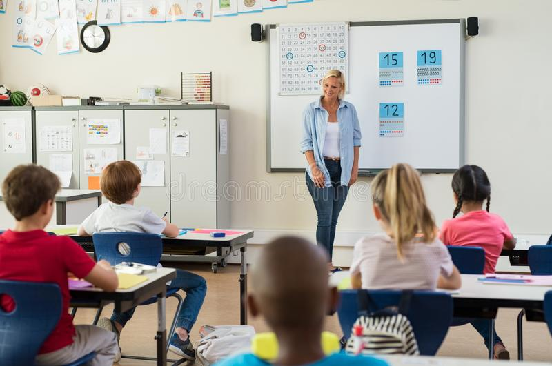 Teacher teaching math to children stock photo