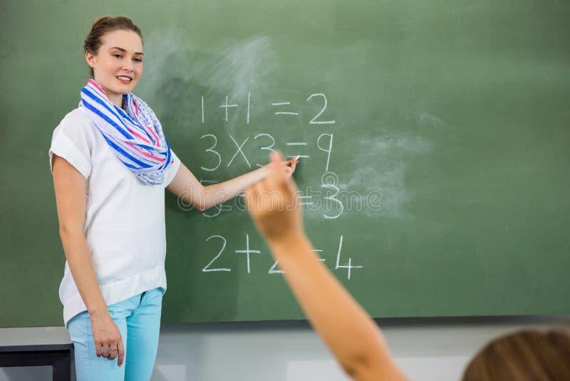 Teacher teaching mathematics in classroom stock image