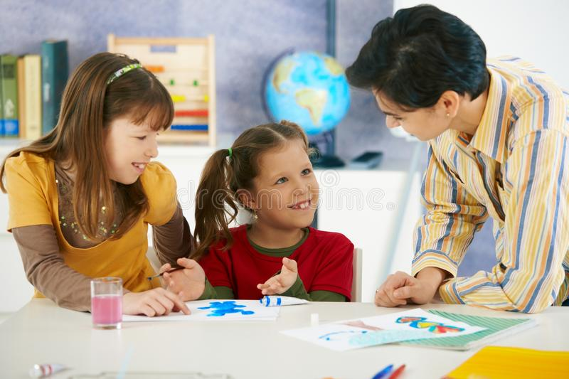 School children and teacher in art class. Teacher teaching painting to elementary age children in classroom at primary school royalty free stock photo