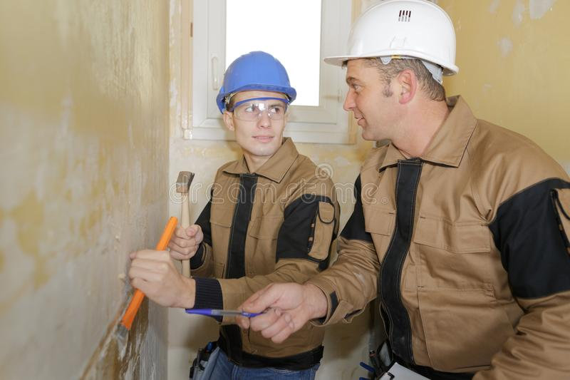 Teacher teaching student to use chisel and hammer royalty free stock image