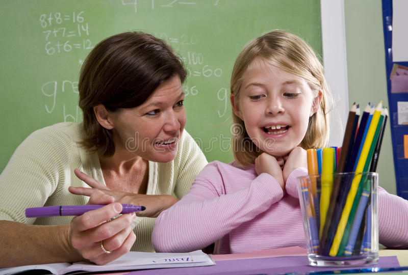 Teacher teaching young student in classroom royalty free stock image