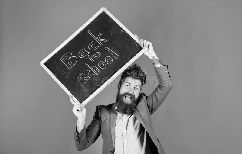 Teacher with tousled hair cheerful about school year beginning. Keep working and be kind to people. Stay positive. Teacher bearded man holds blackboard with royalty free stock photo