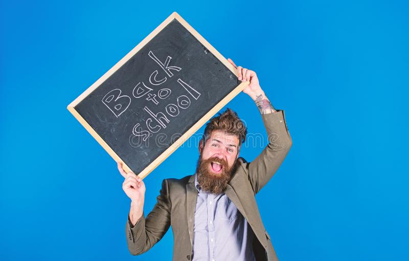 Teacher with tousled hair cheerful about school year beginning. Keep working and be kind to people. Stay positive. Teacher bearded man holds blackboard with royalty free stock photos