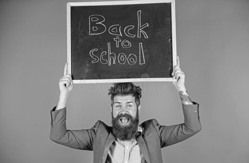 Teacher with tousled hair cheerful about school year beginning. Teacher bearded man holds blackboard with inscription. Back to school blue background. Keep royalty free stock images
